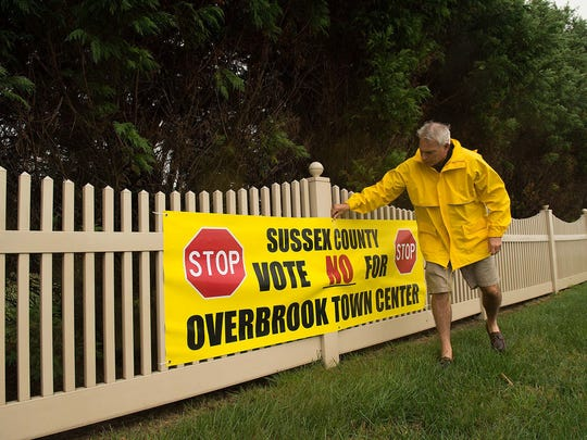 Rich Borrasso straightens a sign that advocates voting