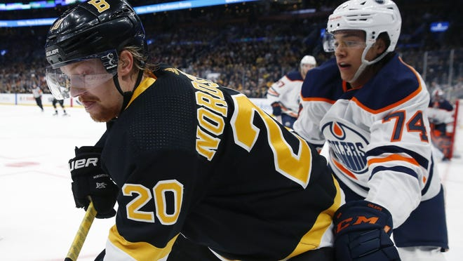 Edmonton Oilers' Ethan Bear battles Boston Bruins' Joakim Nordstrom (left) for the puck during the first period on an NHL hockey game in Boston on Jan. 4, 2020.