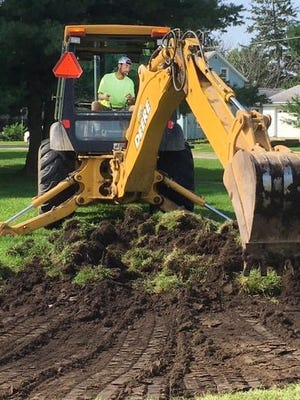 Excavating began Tuesday on the Neponset Veterans' Memorial. Here, village employee Trent Johnson uses some extra muscle to break ground on the project.