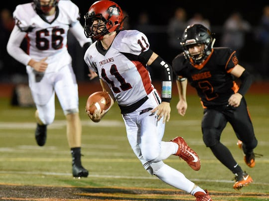 Glens Falls quarterback Joseph Girard scrambles away from Schuylerville's Orion Anderson with team mate Nicholas Danahy at left in the closing seconds of the 2nd quarter on Oct. 6, 2017.
