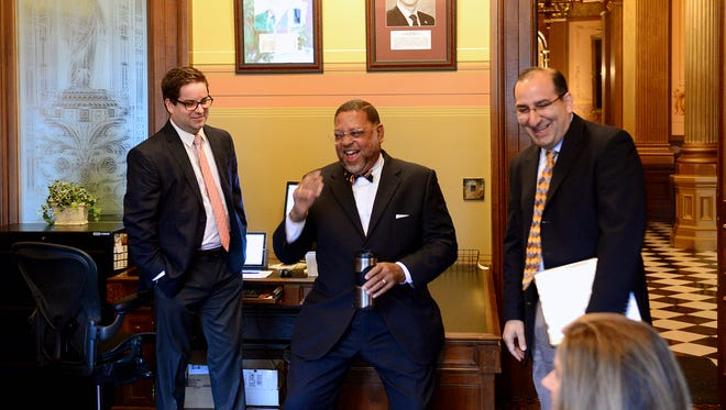 Chief Justice Robert Young, Jr., center, and Justice David Viviano laugh as they talk with others Tuesday, October 13, 2015, in the room before the start of oral arguments in court's former courtroom, now the Senate Appropriations Committee room, in the Capitol Building. The court used this courtroom until 1970, when they moved to the Hall of Justice.