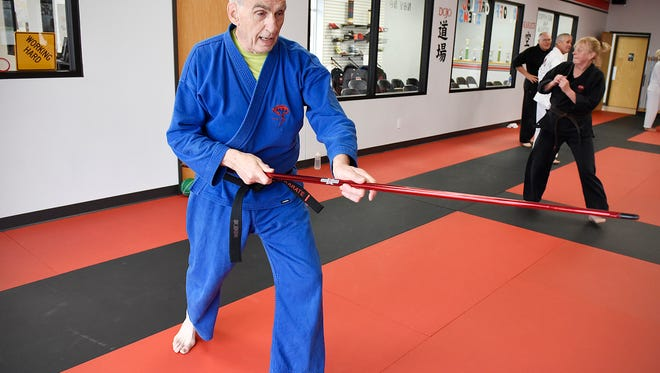 Black belt Ray Dinius works on a series of self-defense moves with a bow during his karate class Thursday at the Dojo Karate in Monticello.