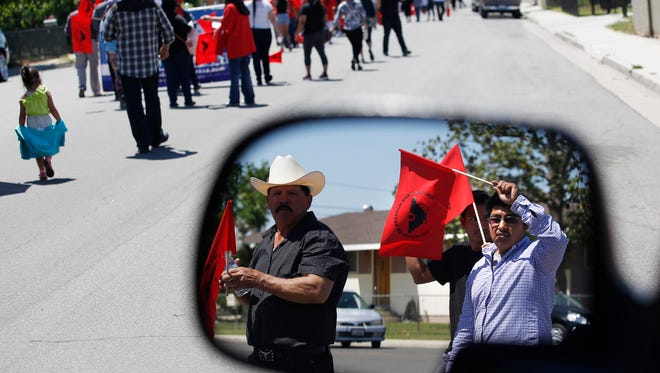 Marchers are shown in the mirror of a truck as they walk from the historic site of Cesar Chavez's march in '66 with hundreds of United Farm Worker members and supporters to protest Donald Trump and celebrate the March 31st birthday of Chavez, the UFW founder, on Sunday, April 17, 2016 in Delano. Calif. The march started at Our Lady of Guadalupe Church and ended at Cesar Chavez Park.