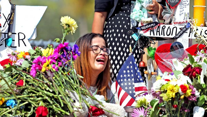 Marjory Stoneman Douglas High School former student Ariana Gonzalez weeps at a cross of slain Marjory Stoneman Douglas coach Aaron Feis, on a hill honoring those killed, Friday, Feb. 23, 2018, in Parkland, Fla. Teachers and staff returned to the school, to begin to organize and prepare to welcome students next week. Over a dozen students and teachers were killed on Valentine's Day in a mass shooting at the high school. (Charles Trainor Jr./Miami Herald via AP)