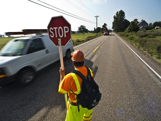 Flagger Zach Rathier watches as cars move through a single lane on U.S. 2 in North Hero in August 2013 as crews work to remove paint lines from the road preparing to new paving.