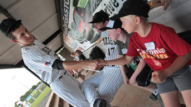 """Monday, June 30, 2014,was """"Kids Run the Park Day"""" at Sims Legion Park on North Marietta Street as the Gastonia Grizzlies hosted the Matinsville Mustangs. Here, (L-R) Grizzlies #27 Ryan Otero shakes hands with coach Ryan Kinney (8) who sits next to fellow kid coach Patrick Manney (8)."""