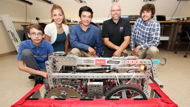 Samuel Dewane, 13, left, Faith Knutson, 14, Ambrose Wiering, 15, President of the Lakeshore FIRST Robotics Program Arrow Guetschow and Ryan Mueller, 18, pose with Valder's Droid Rage Team #3381 robot, Rudy, after introducing their program to Energy Bank, Inc. on Thursday, July 7.