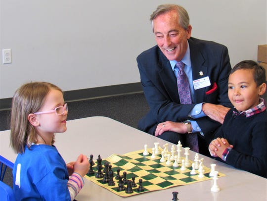County Commissioner Bob Thomas watches a match between 5-year-olds Lily Fisher and Cameron Bogus.