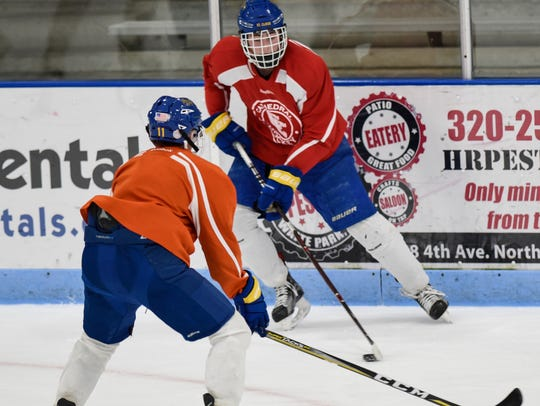 Catehdral's Nate Warner skates with the puck during