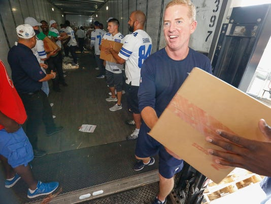 Dallas Cowboys head coach Jason Garrett, team members and The Salvation Army personnel unload 300,000 pieces of donated apparel off a tractor trailer at The Salvation Army Adult Rehabilitation Center Thursday, Aug. 31, 2017. Clothing items include men's, women's and children's tee shirts, fleece, outerwear and rompers worth approximately $500,000. (Ron Baselice/The Dallas Morning News via AP)