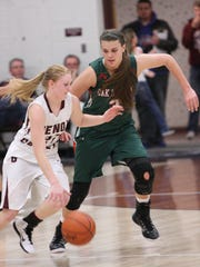 Genoa's Haley Pickard is pressured by Oak Harbor's Andrea Cecil. Photo by Doug Hise.
