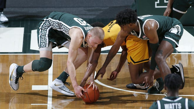 Michigan State's Joey Hauser, left, and Aaron Henry, right, and Oakland's Micah Parrish, center, vie for the ball during the first half of an NCAA college basketball game, Sunday, Dec. 13, 2020, in East Lansing, Mich.