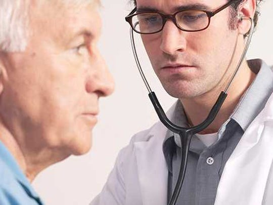 Doctor checking patient's heart with a stethoscope.