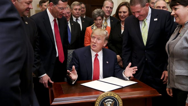 President Donald Trump signs an executive order in February to begin the rollback of environmental regulations put in place by the Obama administration. Trump signed the order in the Roosevelt Room of the White House.