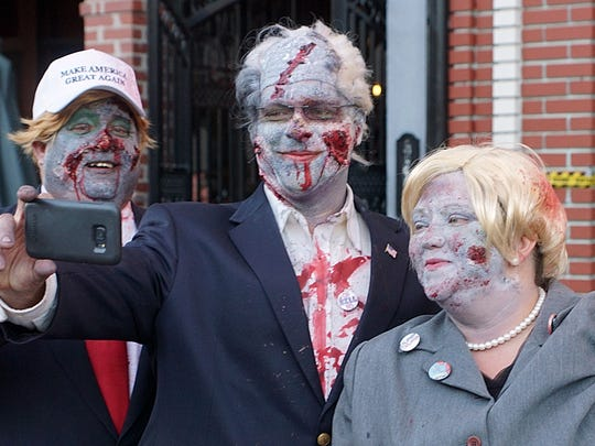 Politicians were not left out of the Zombie Pub Crawl as Don Root (left) as a Donald Trump zombie, Russ Zinck (center) as a Bernie Sanders zombie and Stephanie Rowley (right) as a Hillary Clinton zombie take a selfie as they wait on their secret service motorcade to take them around town.
