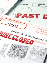 Stack of bills labeled account closed and past due.