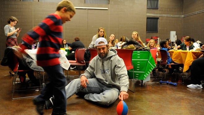 Dale White, 7, plays football with Titans tight end Brett Brackett at Delanie Walker's Turkey Bowl for single mothers Tuesday at East Community Center.