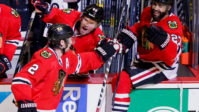 Chicago Blackhawks defenseman Duncan Keith (2) celebrates a game-winning goal with teammates against the Nashville Predators during third period in Game 6 of the first round of the 2015 Stanley Cup Playoffs at United Center.