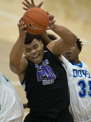 St. Thomas More's Aaron Scott (20) recovers the ball under the hoop in their second round game of the DIAA State Tournament against Dover at Dover High School.