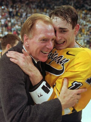 Michigan coach Red Berenson, left, hugs player Bill Muckalt after Michigan defeated Colorado College, 3-2, in overtime to win the NCAA hockey championship on March 30, 1996, in Cincinnati.