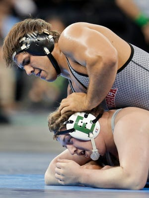 In this March 17, 2016, file photo, North Carolina State's Nick Gwiazdowski, top, controls Eastern Michigan's Gage Hutchison in a 285-pound match during the NCAA Division I wrestling championship in New York. Eastern Michigan plans to drop softball, men's swimming and diving, women's tennis and wrestling at the end of the spring season due to budget cutbacks.