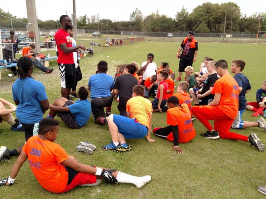 Kirk Broussard, shown talking to kids, worked with two NFL teams and is putting on youth football camp in Pensacola.