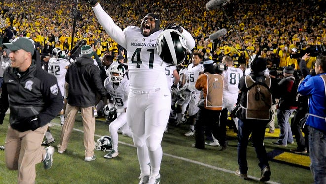 MSU players including Gerald Owens celebrate in Michigan Stadium after  teammate Jalen Watts-Jackson ran back a Michigan fumbled or muffed punt for a touchdown and a 27-23 win Saturday 10/17/2015.