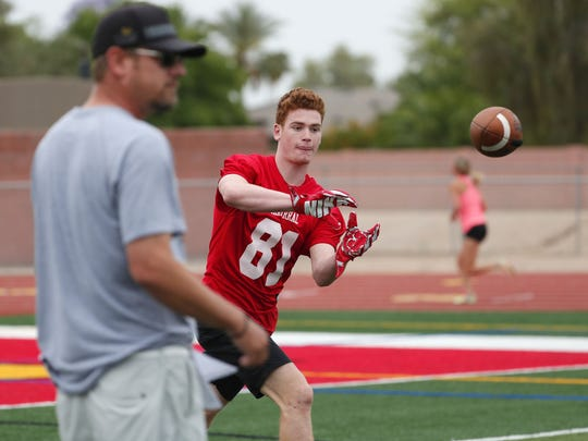 Chaparral High WR Tommy Christakos makes a catch while offensive coordinator Tim Kohner watches during spring football practice in Scottsdale, Ariz. May 1, 2018.