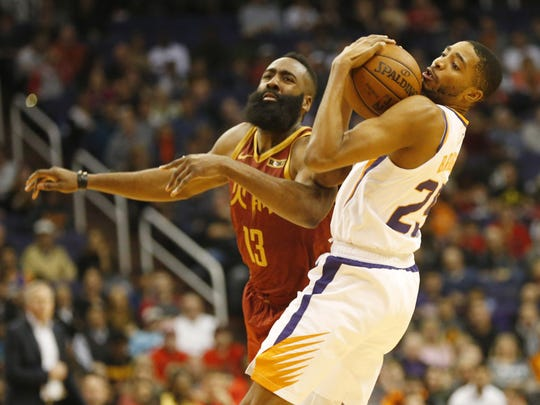 Phoenix Suns forward Mikal Bridges (25) takes the ball from Houston Rockets guard James Harden (13) but was called for a foul during the fourth quarter in Phoenix Feb. 4, 2019.