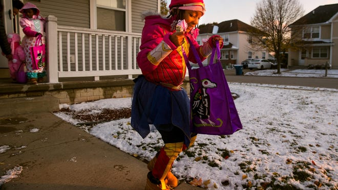Jenae Williams, dressed as Wonder Woman, is all smiles as she peeks into her treat bag while trick-or-treating with friends and family in Springfield Thursday, Oct. 31, 2019.