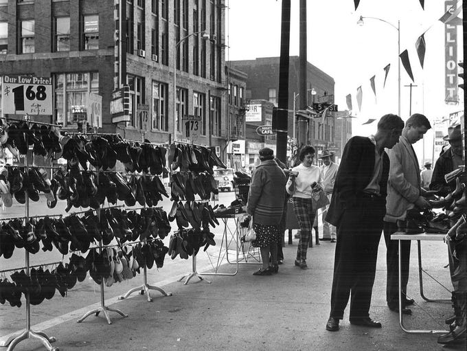 Shoppers search for bargains at a 1958 sidewalk show