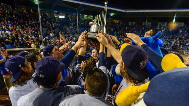 Binghamton Mets players celebrate with the Eastern League championship trophy after a dramatic 2-1 victory in Game 3 on Friday night at NYSEG Stadium.