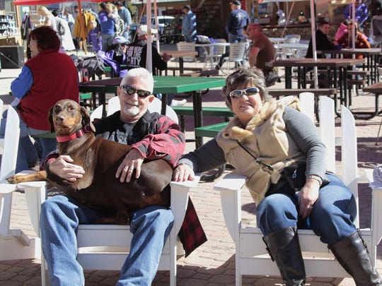 Ruidoso residents Sid and Trina Thomas soak up some sun with their Doberman Zoe at Party on the Mountain Saturday.