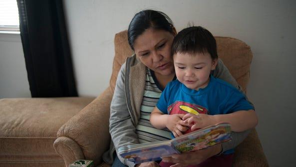 Rhonda Ramirez reads to her son Josiah Lucero, 2, in