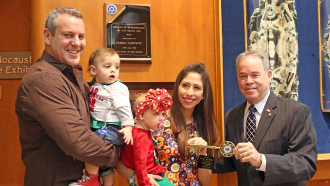 """Rockland County Executive Ed Day presents the key to the county to Millicent """"Ivey"""" Mackle with her husband, Dan and their 14 month-old twins Jack and Emily at the Jewish Community Campus on Dec. 13, 2016. Mackle stood up to hate when an anti-Semitic incident occurred in her neighborhood."""