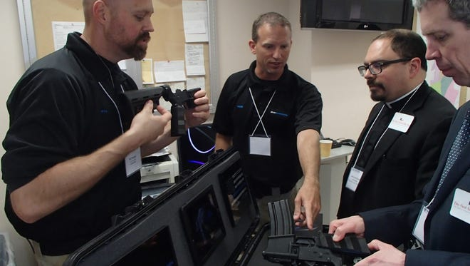 "A demonstration of ""smart guns"" was held at the New Rochelle Police Department in May. Will Murphy and Rob Harvey (from the left) represented Gun Guardian, a safety device developed by law enforcement officers that allows a firearm to be used only by someone with an approved fingerprint or security code. They were speaking with Joe Morris, right, of the Do Not Stand Idly By Campaign, and the Rev. Gawain de Leeuw, rector at St. Bartholomew's Episcopal Church in White Plains and a leader of Westchester United."