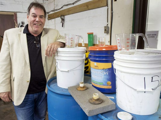 Uniseal Solutions owner Michael Leaman with containers of raw product -- some of the measuring containers and concrete he used to test the sealing solution at another company he owns, Total Asphalt in York. The sealer can penetrate and bind with new and old concrete, sealing in the moisture. He has had a patent approved for his invention.