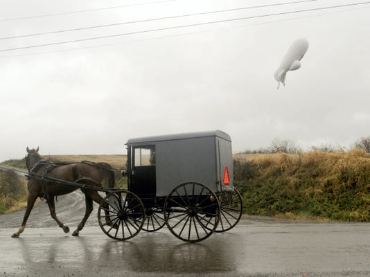 An unmanned Army surveillance blimp which broke loose from its ground tether in Maryland floats through the air about 1,000 feet about the ground while dragging a several thousand foot tether line just south of Millville, Pa., Wednesday, Oct. 28, 2015. (Jimmy May/Bloomsburg Press Enterprise via AP)
