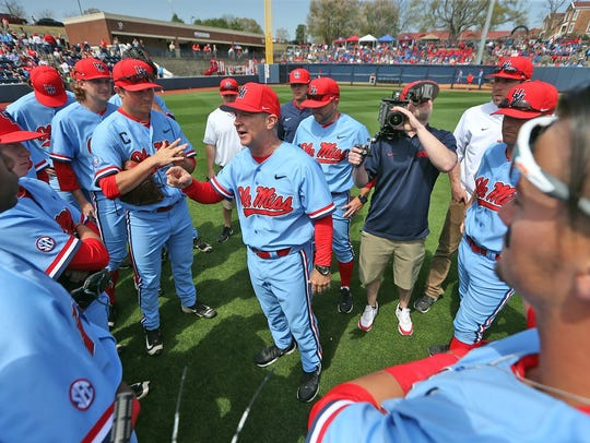 Coach Mike Bianco (center) addresses his team.
