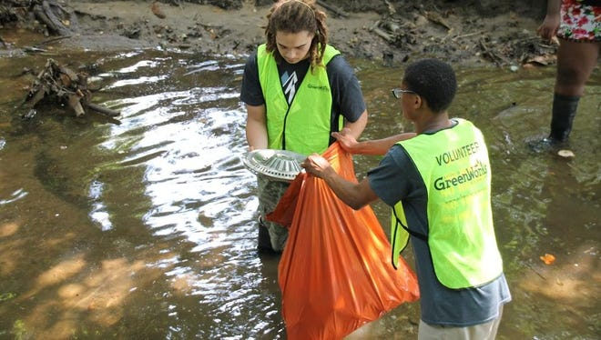 Asheville GreenWorks interns, Immanuel Spears, left, and Terrell Mwetta, right, clean up trash in Moore's Branch creek as part of the Trash Boom pilot program.