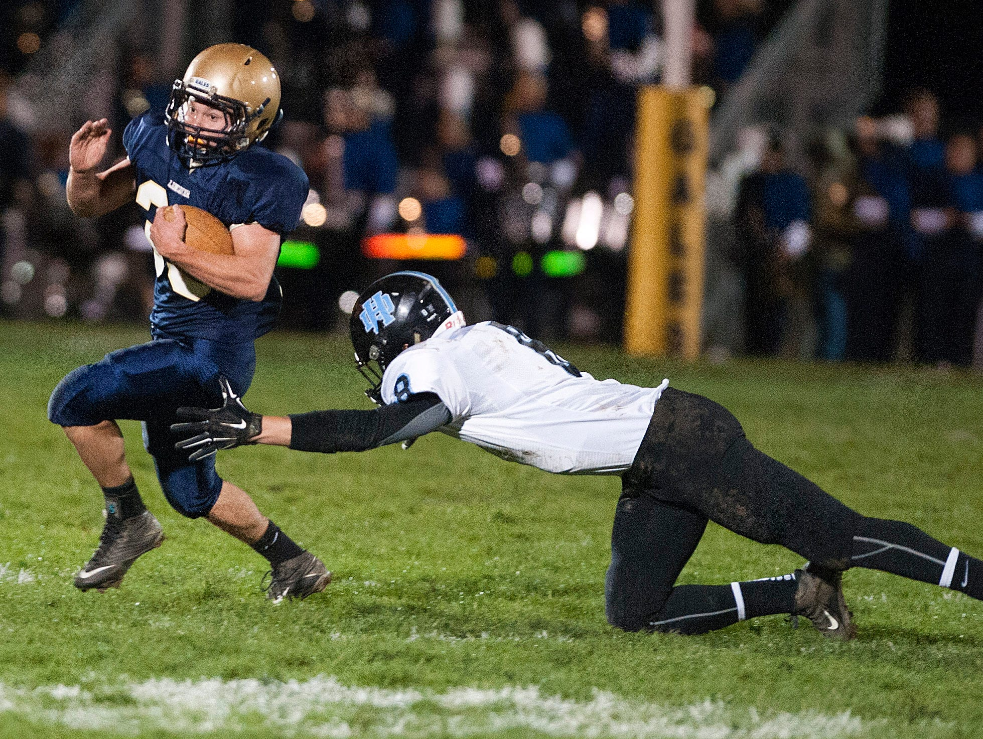 Lancaster's Tyler Carter dodges an attempted tackle by a Hilliard Darby defender during Saturday night's game at Fulton Field in Lancaster.