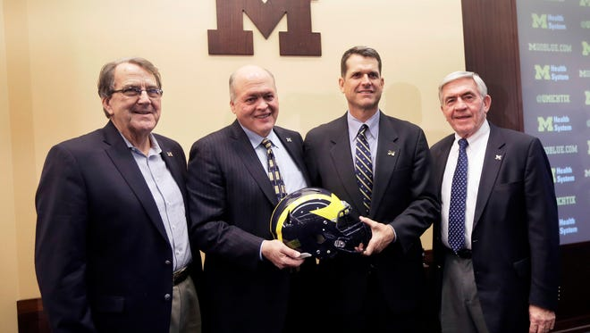 From left, former Michigan coach Lloyd Carr, interim athletic director Jim Hackett, new head coach Jim Harbaugh and former coach Gary Moeller Jim Harbaugh, pose for a photo after Harbaugh was introduced during an NCAA college football news conference Tuesday, Dec. 30, 2014, in Ann Arbor, Mich.