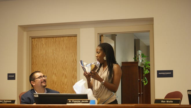 Dr. Francine Jacobs, right, reacts to a surprise gift as Board President Matt Robinson, left, looks on.