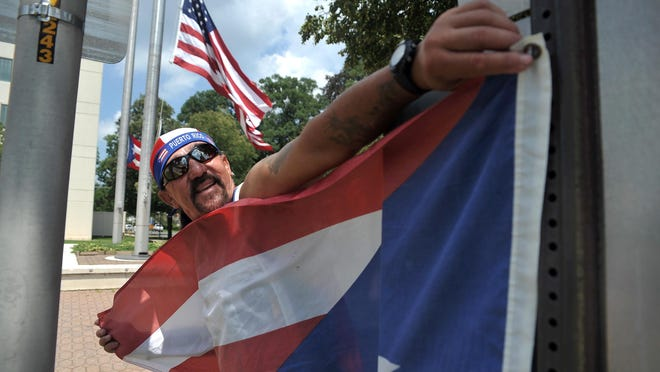 Perennial attendee, Alberto Ortiz of Vineland hangs his own Puerto Rican flag during the Puerto Rican flag raising ceremony at Vineland City Hall, Sunday, Jul. 19, 2015. Staff Photo/Sean M. Fitzgerald