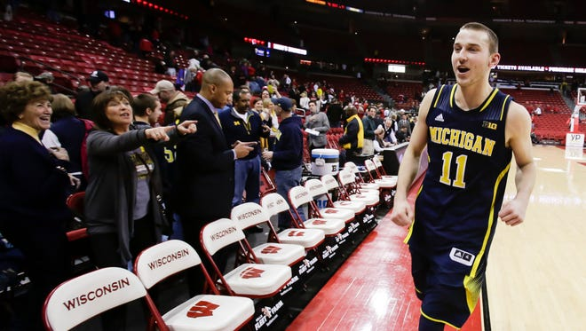 Michigan's Nik Stauskas (11) runs off the court after Michigan upset Wisconsin 77-70 in an NCAA college basketball game Saturday, Jan. 18, 2014, in Madison, Wis. Stauskas had a game-high 23 points.