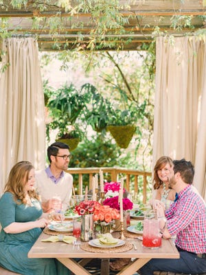 In this photo provided by Brian Patrick Flynn/HGTV.com, the designer Flynn created a cozy, casual outdoor dining space for the 2014 HGTV.com Spring House with a pergola which adds shade as well as weather-resistant drapery that adds privacy. (AP Photo/HGTV.com, Brian Patrick Flynn)