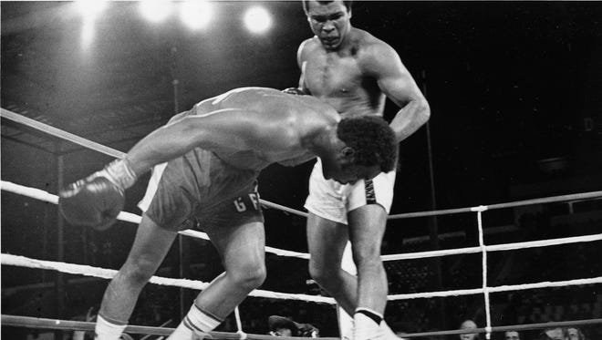 Muhammad Ali watches as defending world champion George Foreman goes down to the canvas in the eighth round of their WBA/WBC championship match in Kinshasa, Zaire.