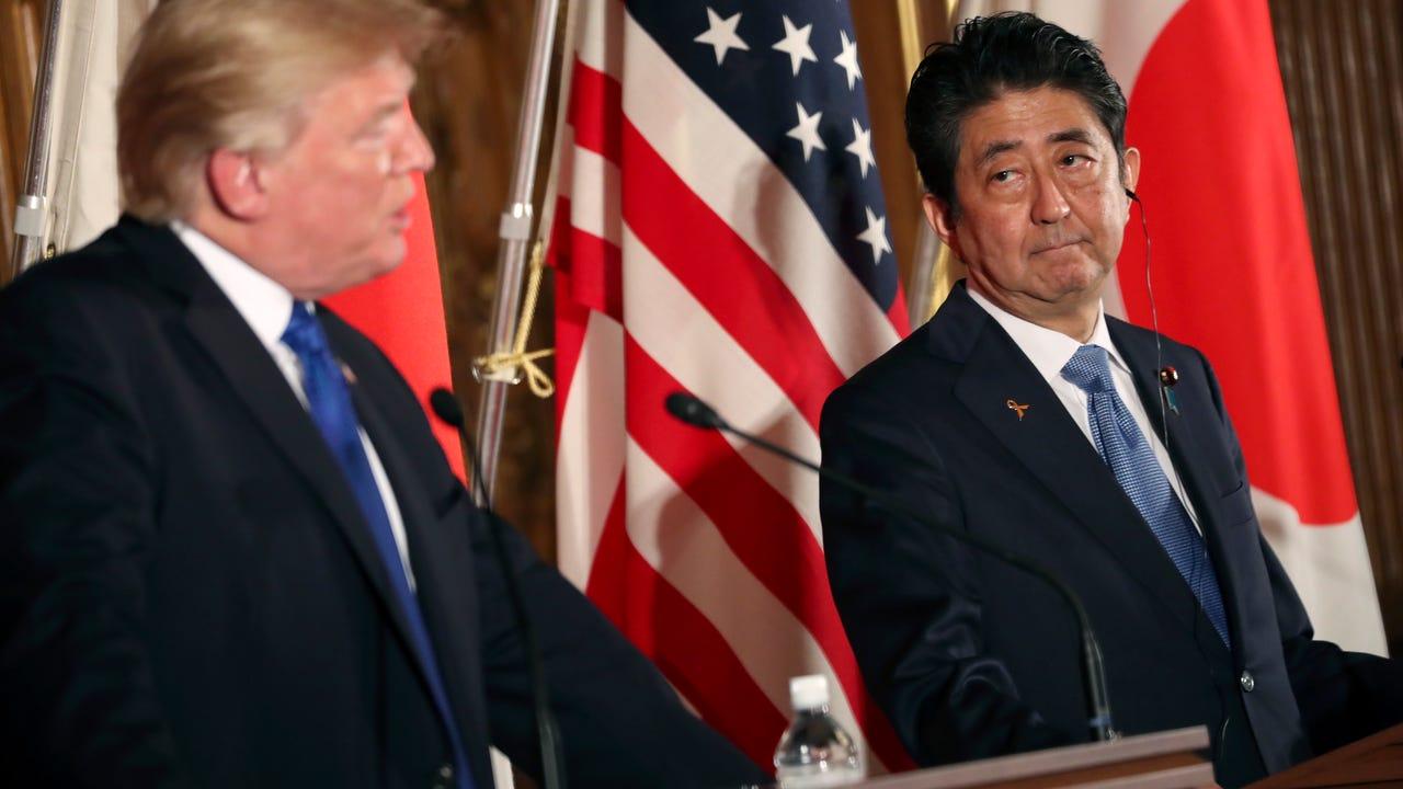 Trump, Abe dump fish food in Tokyo carp pond
