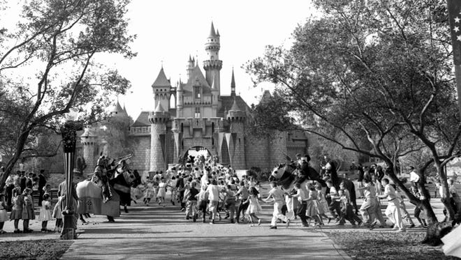 In this July 17, 1955, file photo, children sprint across a drawbridge and into a castle that marks the entrance to Fantasyland at the opening of Walt Disney's Disneyland in Anaheim, Calif. Fantasyland had been closed until late in the day.