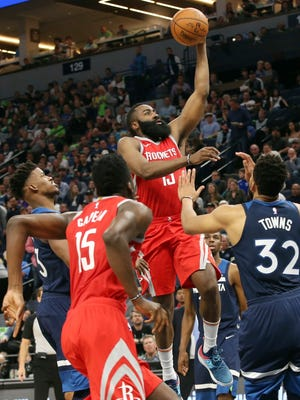 Rockets' James Harden, center, rises up to shoot as Timberwolves' Jimmy Butler, left, and Karl-Anthony Towns, right, look on during the second half on Monday.